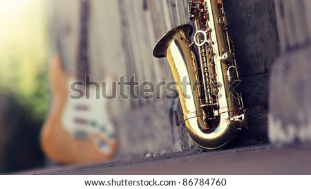 old grungy saxophone with defocused guitar in the background - stock photo