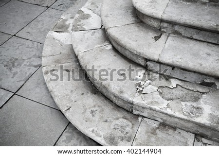 Old grungy white ancient stone stairway with round stairs - stock photo