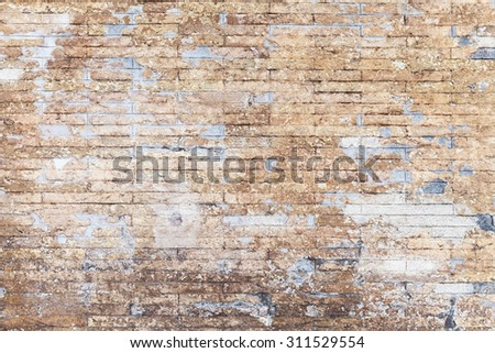 Old grungy yellow brick wall background texture with damaged stucco layer - stock photo