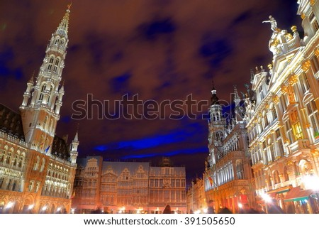 Old guildhalls and the City Hall of Brussels illuminated by night in Grand Place, Brussels, Belgium - stock photo