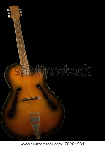Old guitar on black background - stock photo
