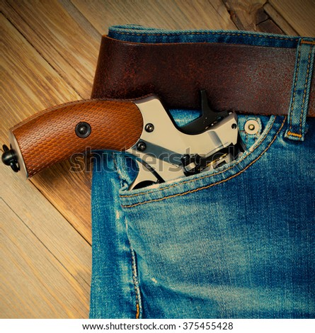 old gun in the pocket of vintage blue jeans. Instagram image filter retro style - stock photo