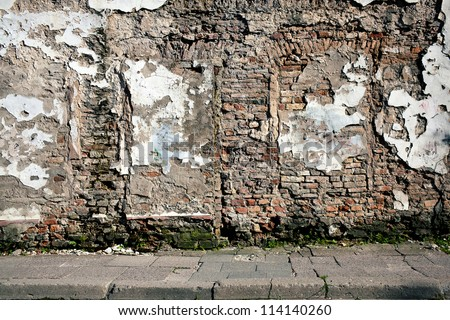 Old gungy wall with immured door - stock photo