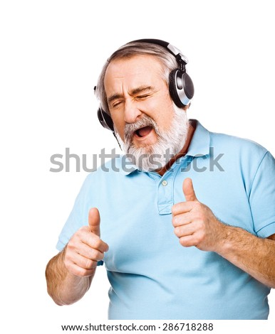 Old guy listening to music on his headphones - stock photo