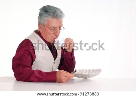 old guy with newspaper and tea at table