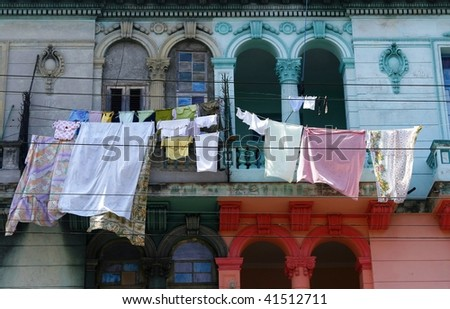 Old half-renovated colonial building in Havana, Cuba. Fresh laundry flapping in the wind - stock photo