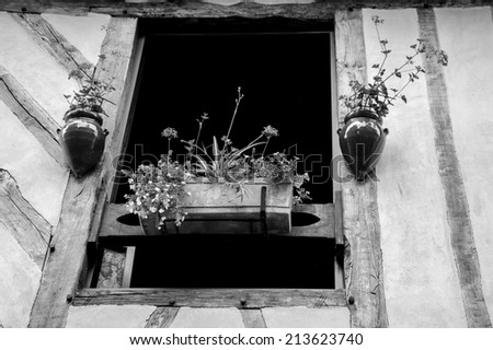 Old half timbered house house decorated with flowers.  Dol de Bretagne, Brittany, France. Aged photo. Black and white.
