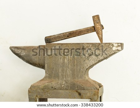Old hammer and anvil tools against white clay wall as a background. - stock photo