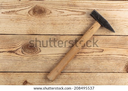 Old hammer on a wooden background