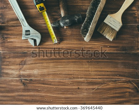 Old hammer, ruler, brush and other work elements on the wood table