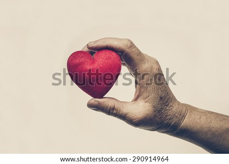 old hand holding a red heart  - stock photo