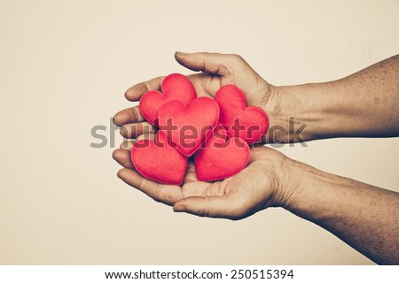 old hand holding a red heart / Love for the elderly people