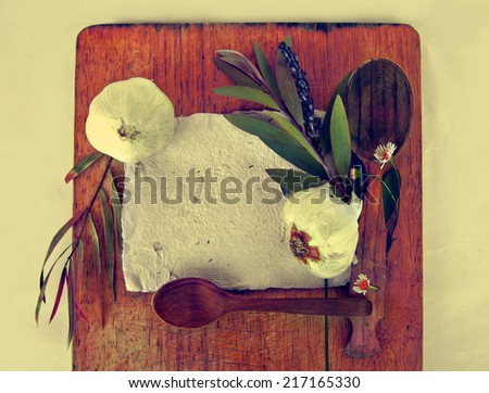 Old hand made papers with lavender flowers, garlic, wooden spoons and acorns over dark surface with copy space - stock photo