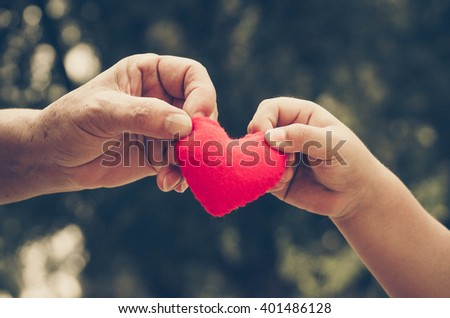 old hand of the elderly and a young hand of a baby holding a red heart together in old vintage tone - stock photo