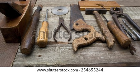 Old hand tools in a row. Old rusty and dirty carpenter`s hand tools lying in a row on wooden table. - stock photo