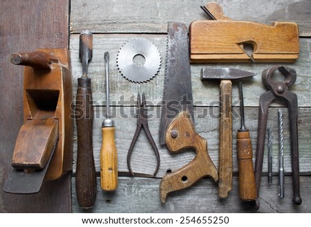 Old hand tools table. Old rusty and dirty carpenter hand tools lying on a wooden table background.  - stock photo