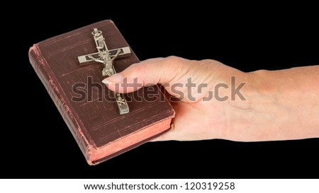 Old hand (woman) holding a very old bible, isolated on white - stock photo