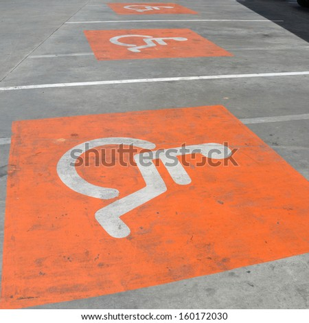Old handicap sign on the floor of car parking. - stock photo