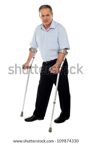Old handicapped man with a walker  standing against white background - stock photo