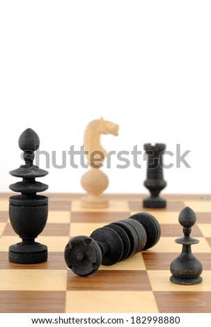 Old, handmade chess pieces in font of a white background
