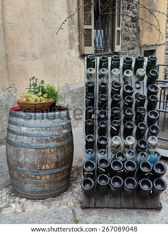 Old handmade Wine barrel and bottle outside a bar in Italy