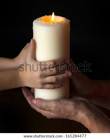 old hands and young hands holding a candle - concept