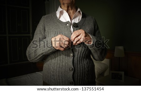 Old hands of an unrecognizable senior woman buttoning her self. - stock photo
