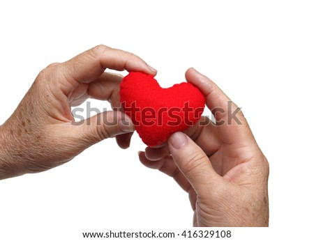 old hands of the elderly holding a red heart - stock photo