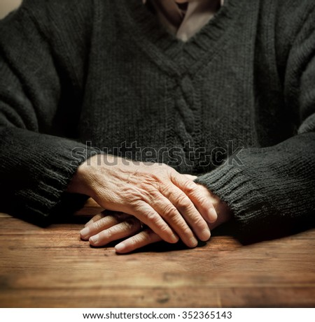 Old hands on a wooden table with dramatic lighting