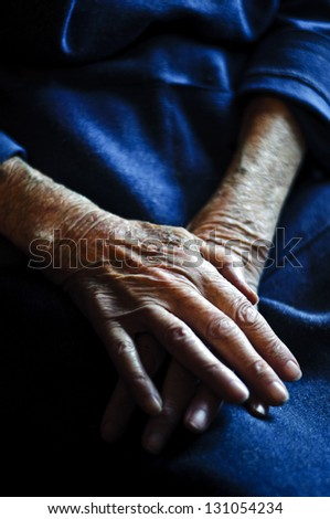 old hands on blue dress - stock photo