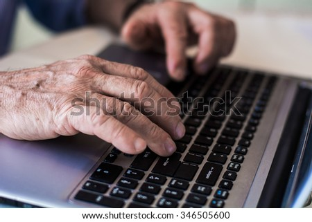 Old hands on the keyboard  - stock photo
