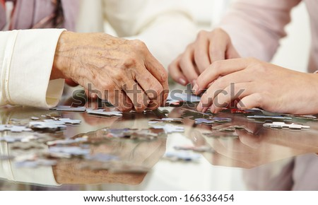 Old hands solving jigsaw puzzle in a nursing home - stock photo