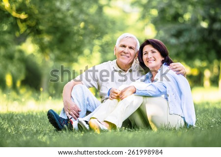 Old. happy Mature couple walks in the park in summer day - stock photo