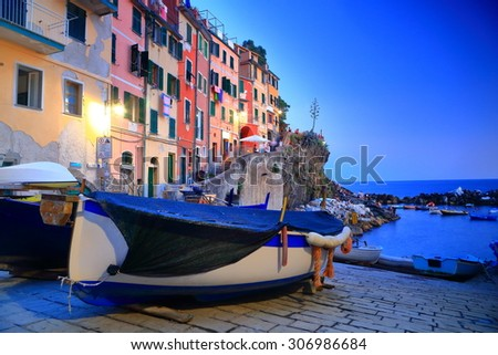 Old harbor of Riomaggiore with traditional buildings and boats on the shore at dusk, Cinque Terre, Italy - stock photo