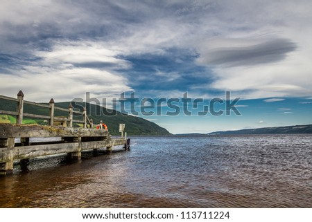 Old harbor over Loch Ness in sunny Scotland - stock photo