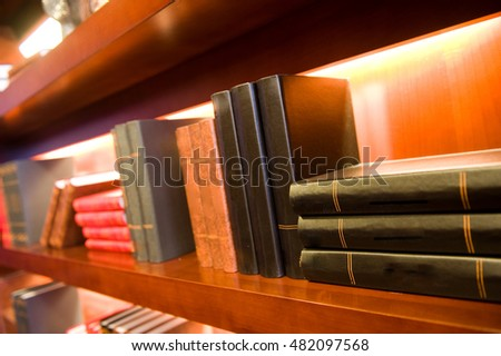 Old hardcover books on a bookshelf.