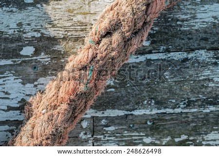 Old hawser rope sitting atop a old ruin of a rowboat - stock photo