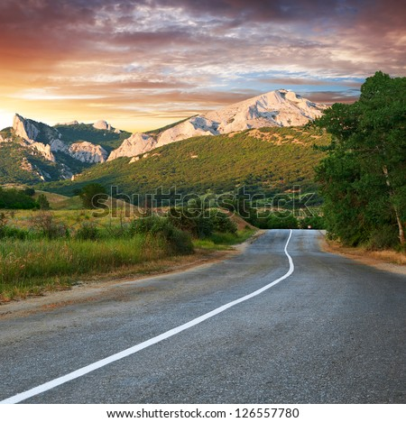 Old highway against mountains and a cloudy sky at the sunset - stock photo