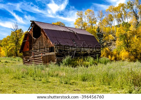 Old historic barn surrounded by fall color along road to Capitol Peak near Aspen Colorado - stock photo