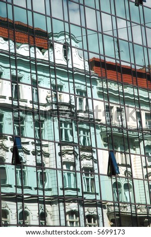 Old, historic building reflecting in glass windows of new, modern building - stock photo