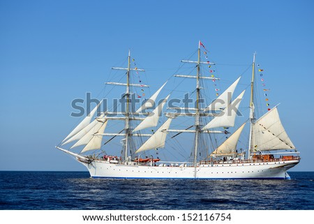 old historical tall ship with white sails in blue sea - stock photo