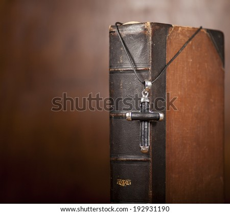 Old Holy Bible and cross on wooden background. - stock photo