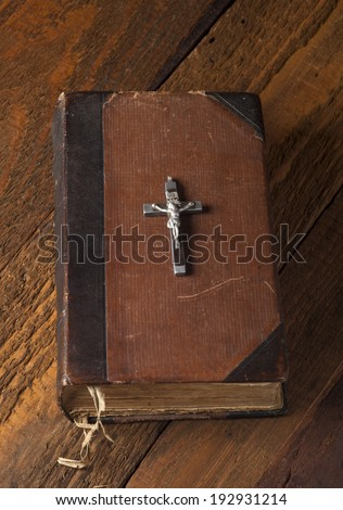 Old Holy Bible and Crucifix on wooden background. - stock photo