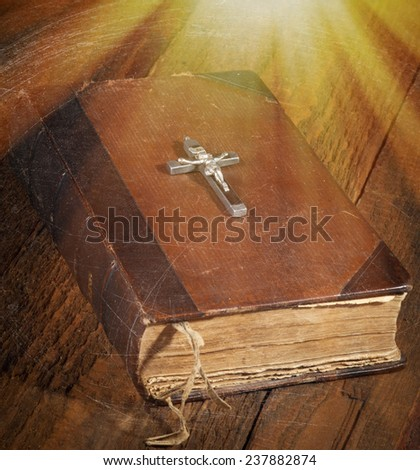 Old Holy Bible and Crucifix on wooden background. With special lighting effect. - stock photo
