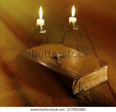 Old Holy Bible, candles and Crucifix on wooden background. With special lighting effect. - stock photo