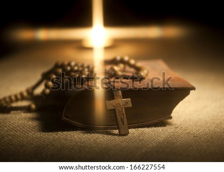 Old Holy Bible, Rosary Beads and Candle. - stock photo