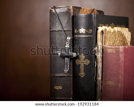 Old Holy Bibles and cross on wooden background. - stock photo