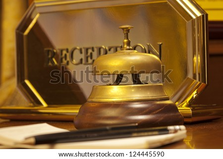 old hotel bell on a brown wood stand - stock photo