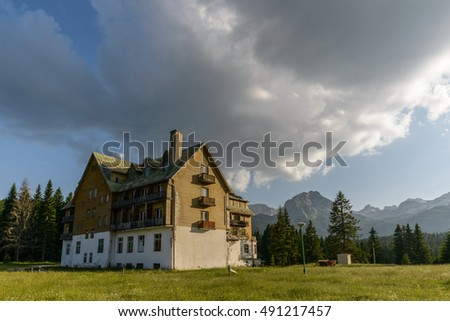 Old hotel with dramatic sky and mountain.