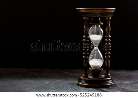 old hourglass on dark background with copy space